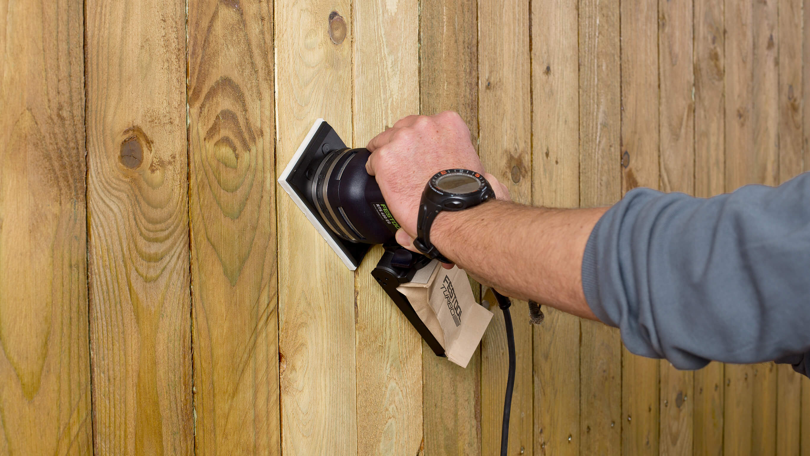 Sanding a wooden fence